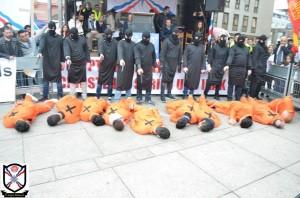 Mit drastischen, gestellten Szenen – wie hier am 7. März bei der Großdemonstration in Mainz – machen die Assyrer auf die Situation in ihrer Heimat und die Verbrechen der IS-Terroristen aufmerksam. (Quelle: AJM / www.Qolo.de)