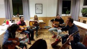Rolf Springer erklärt den Jugendlichen einige Grundlagen zur Gitarre (Quelle: Jugendverbandsarbeit mit jungen Geflüchteten)