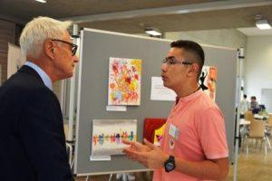 B'shayno-Mitglied Eilom Keriakos zeigt Martin Pantke, 2. stellvertretender Bürgermeister der Stadt Paderborn, Kunstwerke, die bei kreativen Projekten entstanden sind. (Quelle: AJM e.V./djoNRW)
